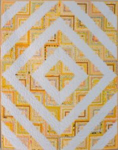 yellow and white log cabin quilt