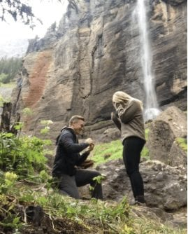 A wedding photographer in DC expertly captures the moment a man proposes to his girlfriend in front of a waterfall on a green hiking trail by the mountains and rocks