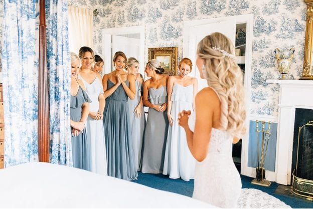 seven bridesmaids reacting to the bride's final look before the wedding ceremony