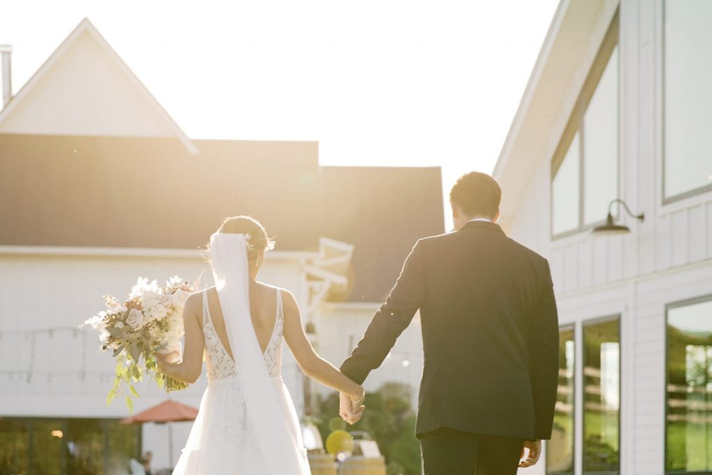 newlyweds walking outside during golden hour