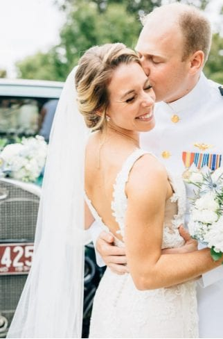 A wedding photographer in Maryland captures a loving newly married couple standing in front of a car in each other's embrace as the groom wearing a white suit kisses the bride's cheek, and she smiles with her eyes closed, holding a bouquet of white flowers